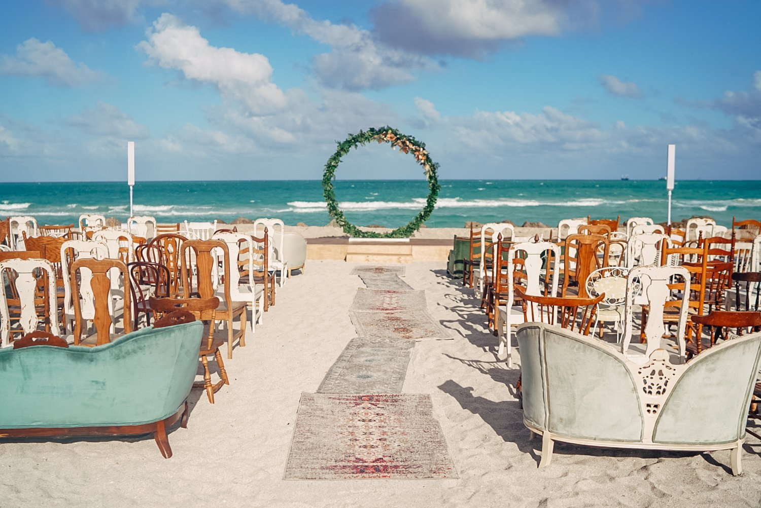 Beach ceremony with armchairs and circular arch behind Faena hotel in Miami